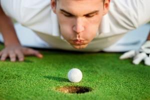 Игрок гольфа помогает мячу, дуя на него